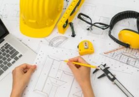 hand-over-construction-plans-with-yellow-helmet-and-drawing-tool_1232-2909