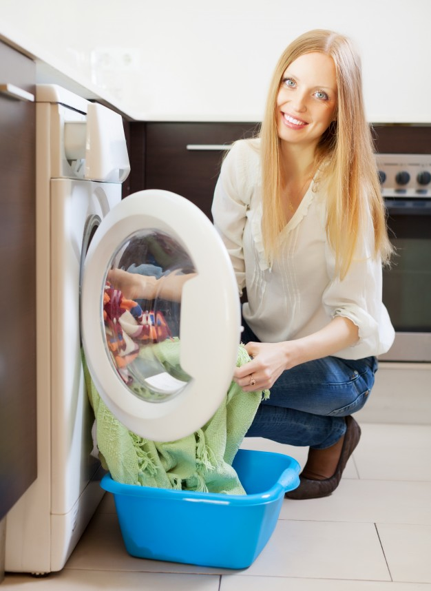happy-long-haired-woman-loading-clothes-into-washing-machine_1398-753